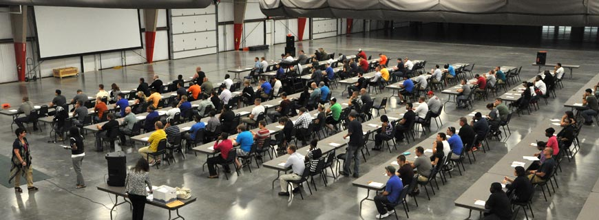IMAGE SHOWING APPLICANTS TAKING WRITTEN EXAMINATION IN A LARGE ROOM WITH SEVERAL ROWS OF TABLES